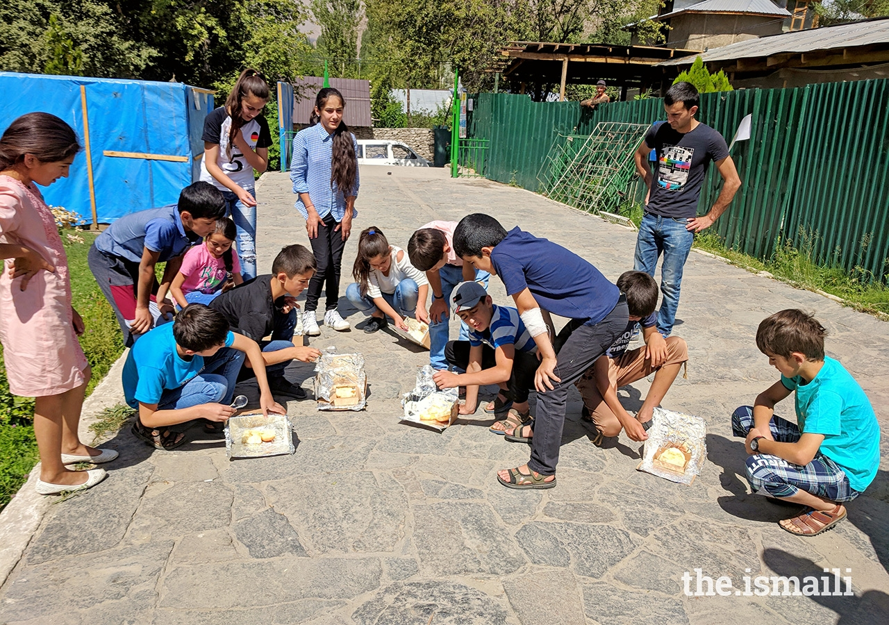 Students harness the power of the sun in their solar ovens to melt cheese on bread.