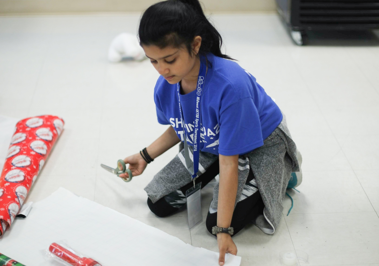 Alyssa Merchant takes a break from playing basketball to wrap a toy to donate during the I-CERV Wrap-A-Thon.