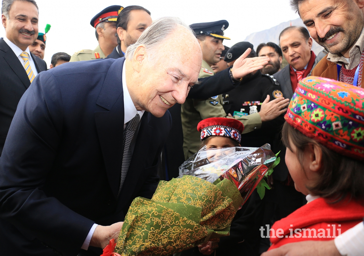 Mawlana Hazar Imam is presented with a bouquet of flowers upon his arrival at the Gilgit airport