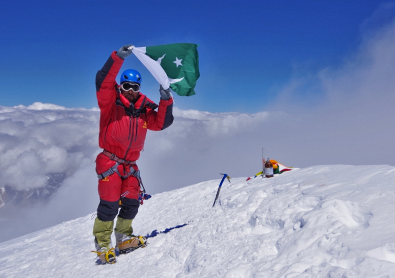 Sirbaz Khan displays the flag of Pakistan after reaching the top of K2.