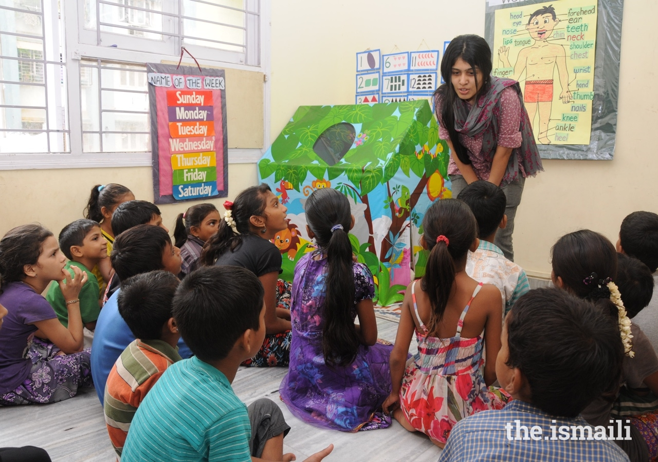 Children listen attentively to Sonia Mackwani during a storytelling session.