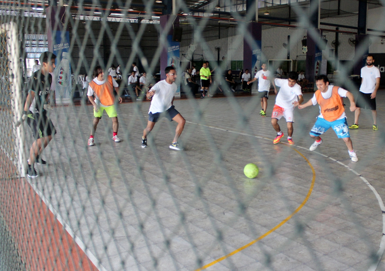 Teams compete in a fast-paced Futsal match (a form of indoor football / soccer). Salman Motani