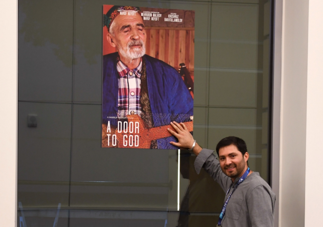 "Maruf Noyoft next to a poster of his film, ""A Door to God."""