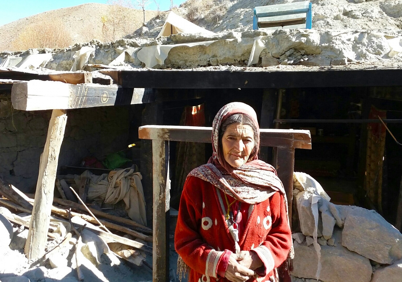 A woman in Phandar, Ghizer stands before the remnants of her home, which collapsed in the 26 October earthquake.