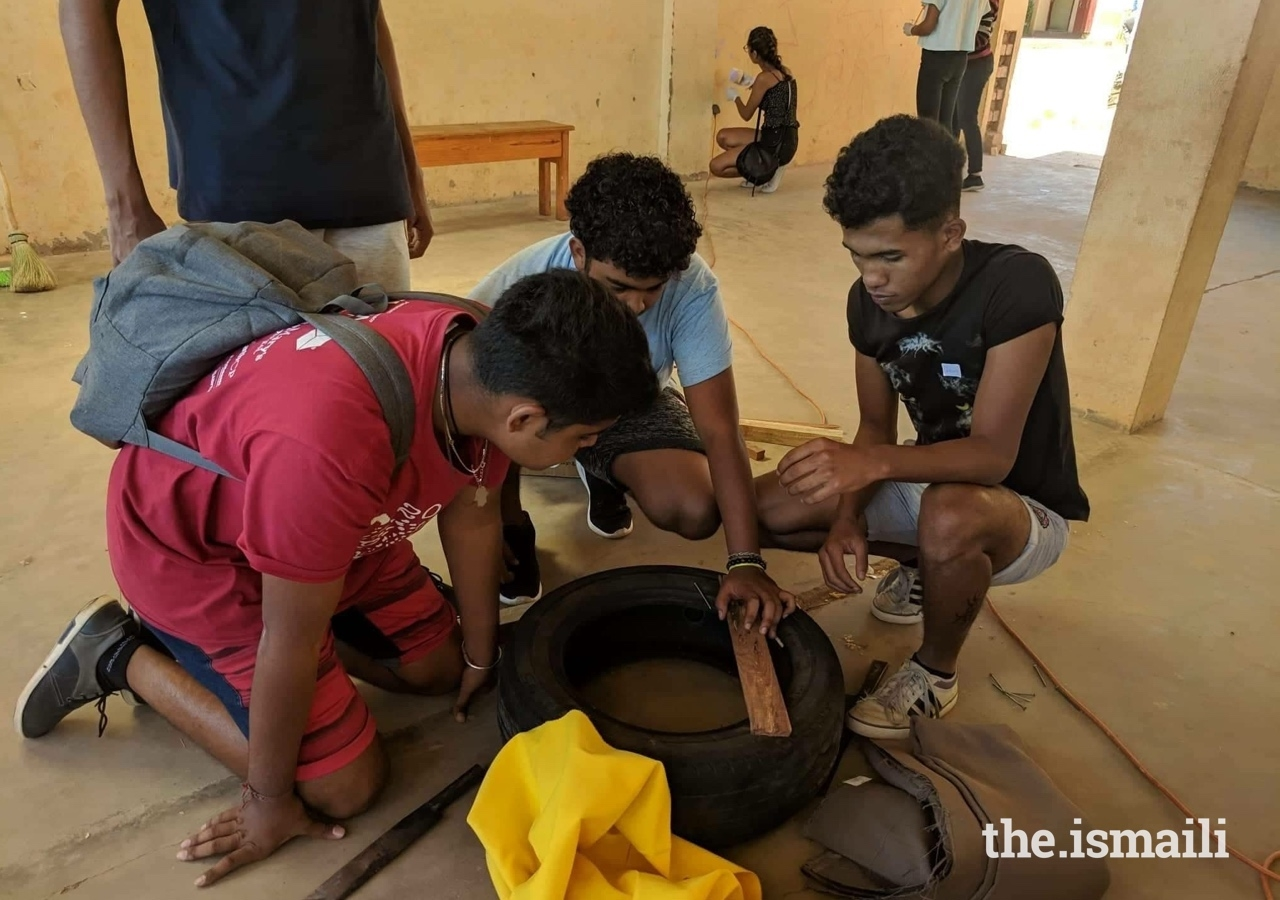 Secondary Bait-ul ilm students making a footstool with recycling materials.