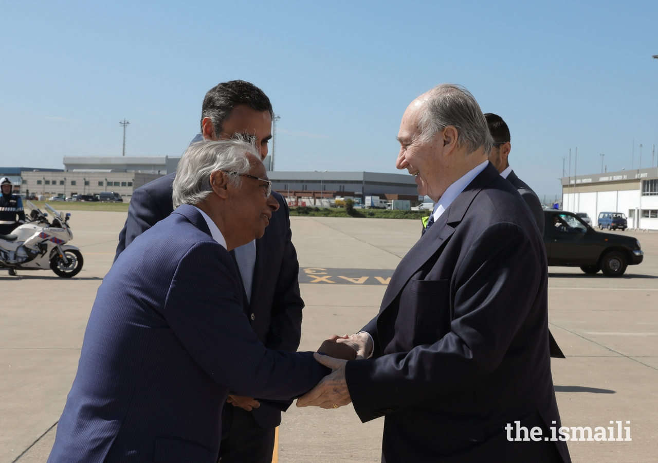 Mawlana Hazar Imam is greeted by Nazim Ahmad, Diplomatic Representative of the Ismaili Imamat to the Portuguese Republic, as Rahim Firozali, President of the Ismaili Council for Portugal looks on.