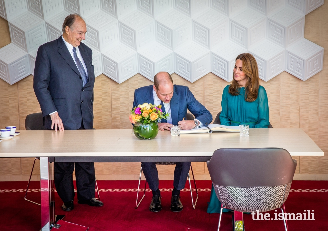 The Duke of Cambridge signs the guest book at the Aga Khan Centre, as Mawlana Hazar Imam and the Duchess of Cambridge look on.