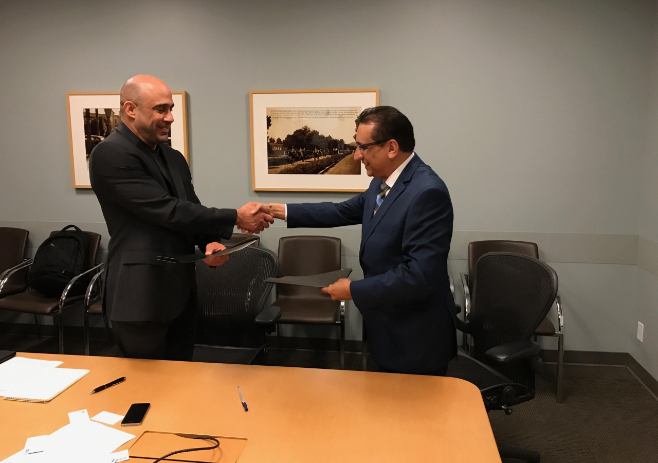 Dr. Mirza Kajani, Chairperson, Aga Khan Health Board for USA, and Greg Szekeres, Deputy Director of UCLA's Center for World Health, exchange documents recording the MOU between Aga Khan Health Service/Aga Khan University and UCLA's School of Medicine.
