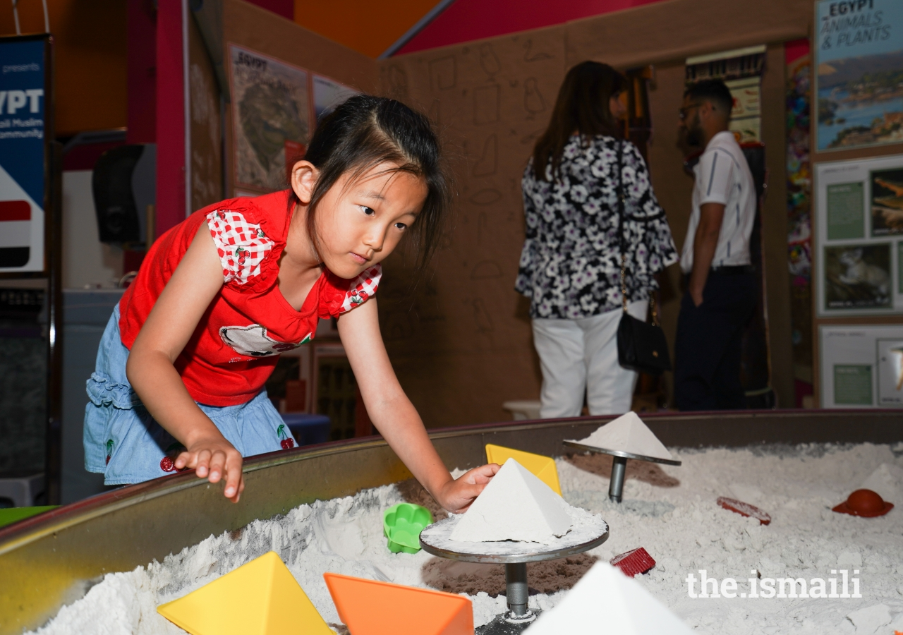 A young child makes sand pyramids at the interactive Egypt exhibit.