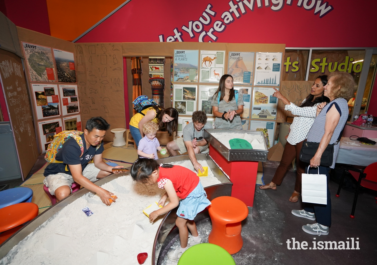 Children and parents play at the Egypt exhibit while Christina Deigni engages in conversation about Al-Azhar Park.