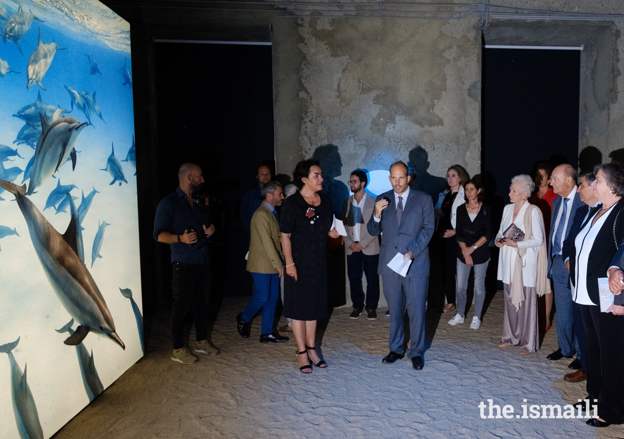 Prince Hussain presents a photo of dolphins to Marta Lorenço, Director of Portugal's National Museum of Natural History and Science, as Prince Amyn and guests look on.