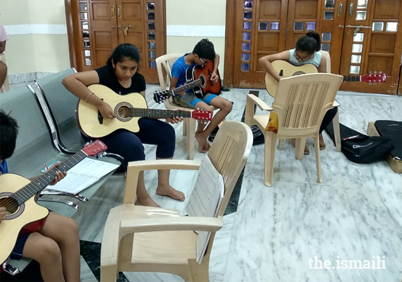 Participants learning the guitar at AKYSB's Music Matters programme. Studies have shown that Art education, including musical education, helps in brain development and promotion of multiple intelligences in children.