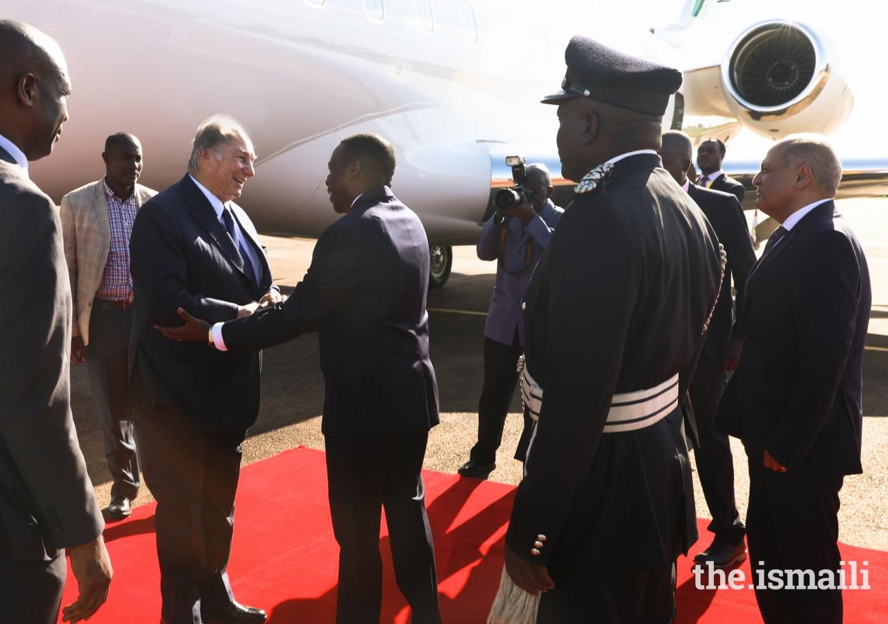 Attorney General Hon. William Byaruhanga greets Mawlana Hazar Imam at Entebbe Airport, as Ismaili Council for Uganda President Minaz Jamal looks on.