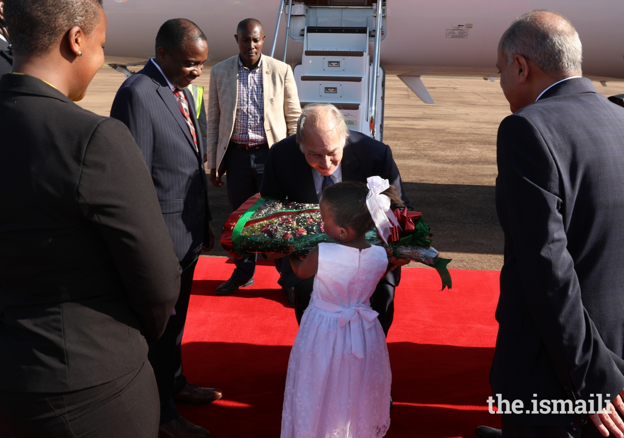 Mawlana Hazar Imam is presented a bouquet of flowers upon his arrival in Uganda.