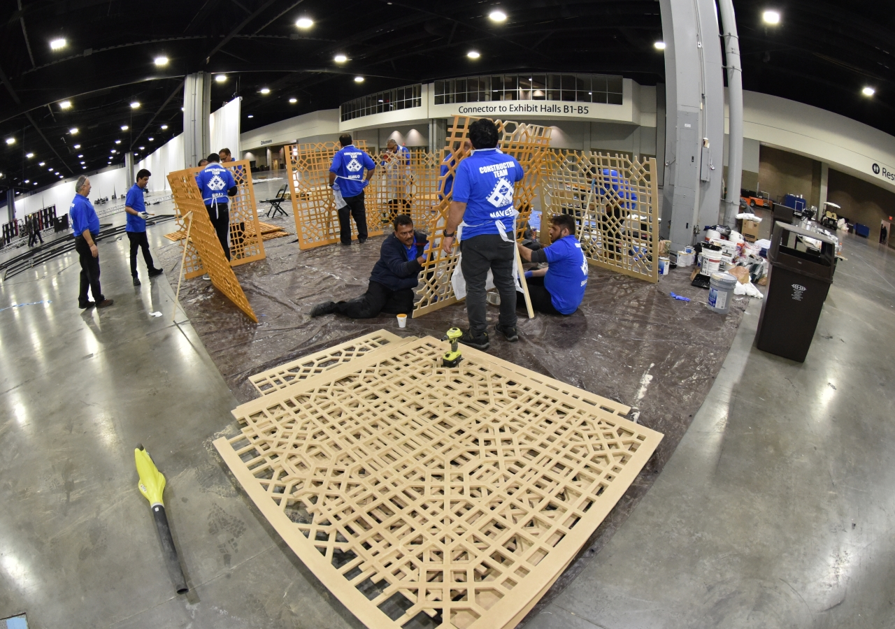 Volunteers from the stage construction team assemble pieces of the mashrabiya panels.