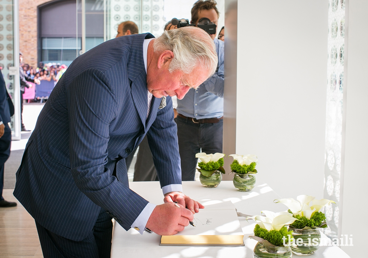 HRH The Prince of Wales signs the guest book at the Aga Khan Centre.