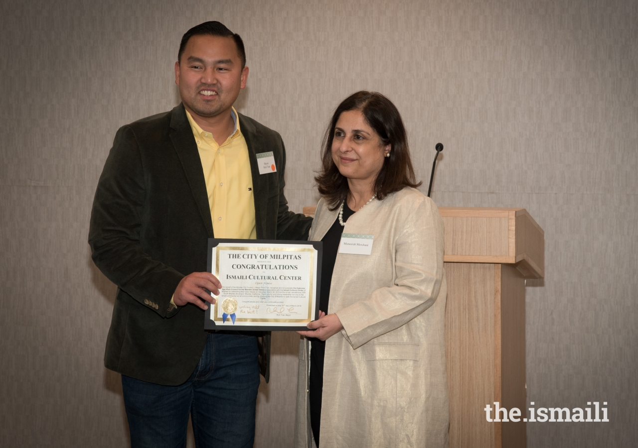 President Muneerah Merchant accepting a congratulatory letter from Mayor Richard Tran of the City of Milpitas.