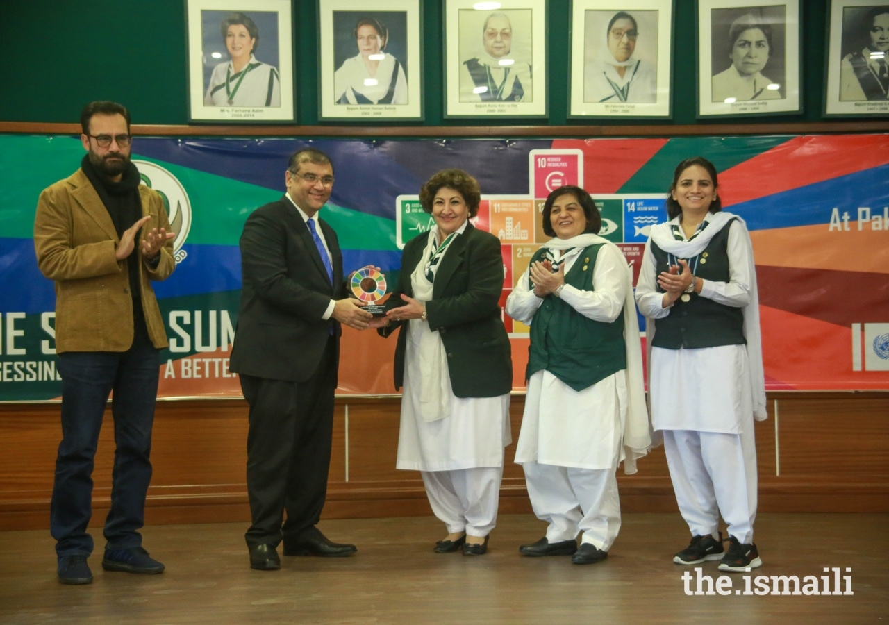 Hafiz Sherali, President of the Ismaili Council for Pakistan presents a token of appreciation to Senator Nuzhat Amir Sadiq, National Commissioner of the Pakistan Girl Guides Association.