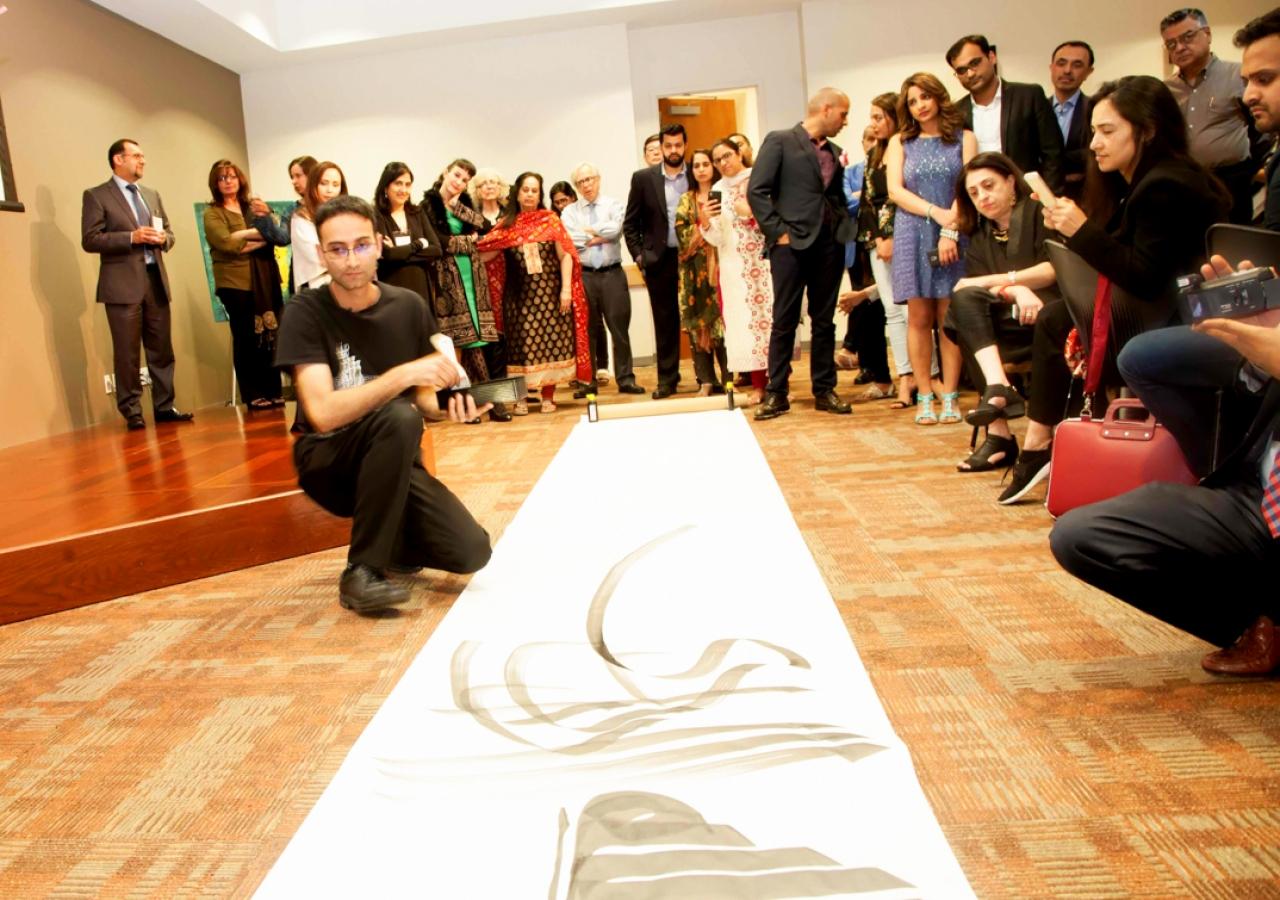 Musicalligrapher Bahman Panahi illustrating his work at Plano Jamatkhana during the Art Symposium dinner.