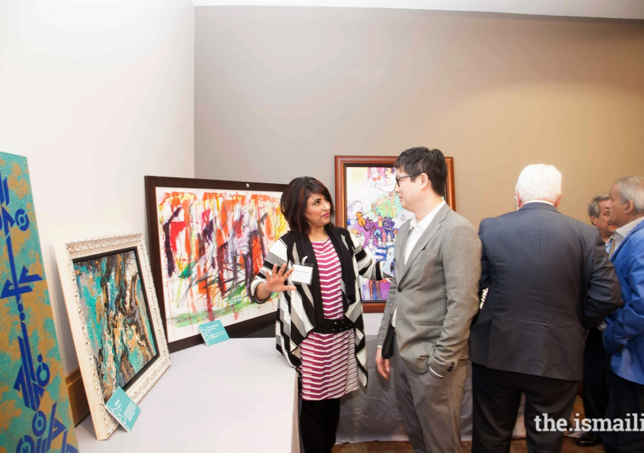 Samina Hooda showing a guest some of the artwork exhibited at the Jubilee Arts Festival.