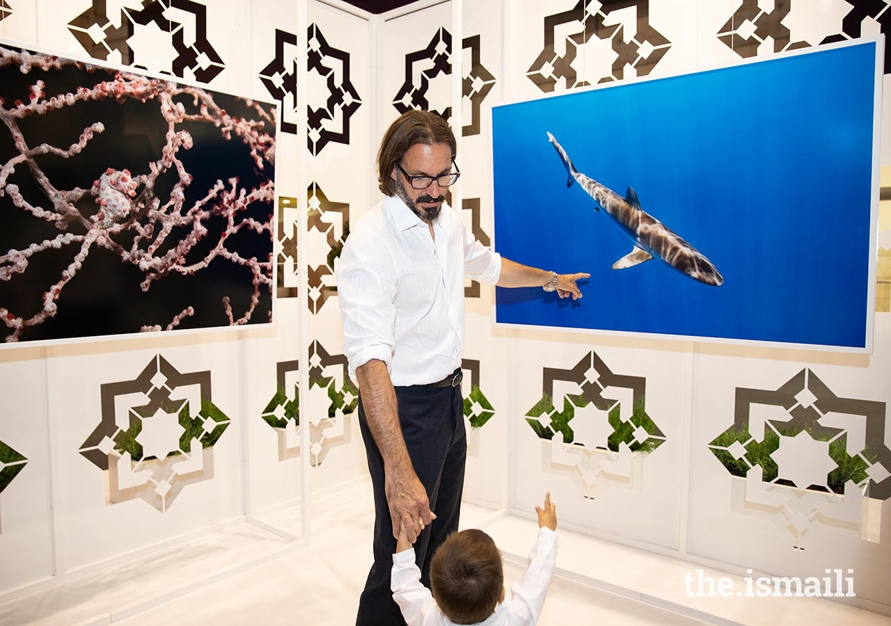 Prince Rahim shows Prince Irfan a photograph taken by Prince Hussain at the Nature Photographic Exhibition in Lisbon.