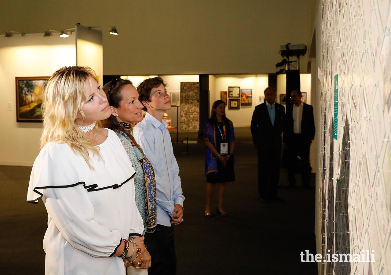 Princess Zahra, Miss Sara Boyden, and Master Iliyan Boyden view artwork at the International Art Gallery during the Diamond Jubilee Celebration.