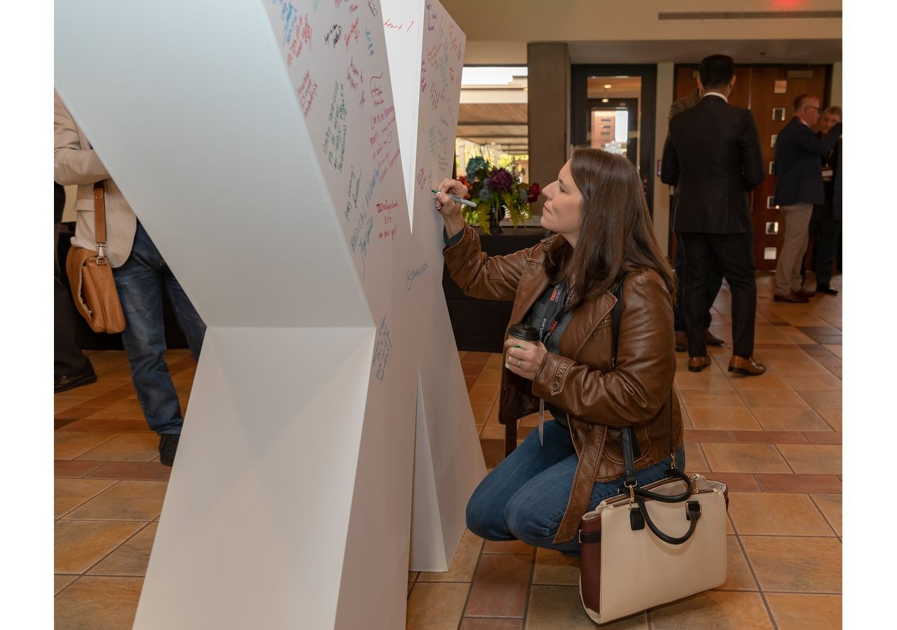 """Attendees signing a large """"X"""" with positive messages while networking and awaiting the presentations by speakers at the TEDxSugarLand."""