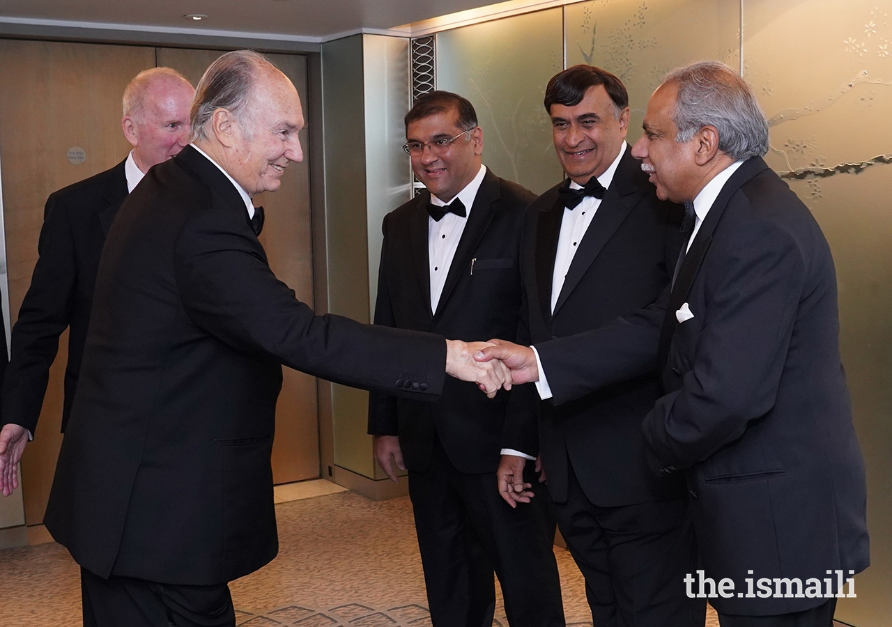 Mawlana Hazar Imam is greeted by President of the Ismaili Council for the UK Liakat Hasham, Head of the Department of Jamati Institutions Dr Shafik Sachedina, and President of the Ismaili Council for Pakistan Hafiz Sherali.