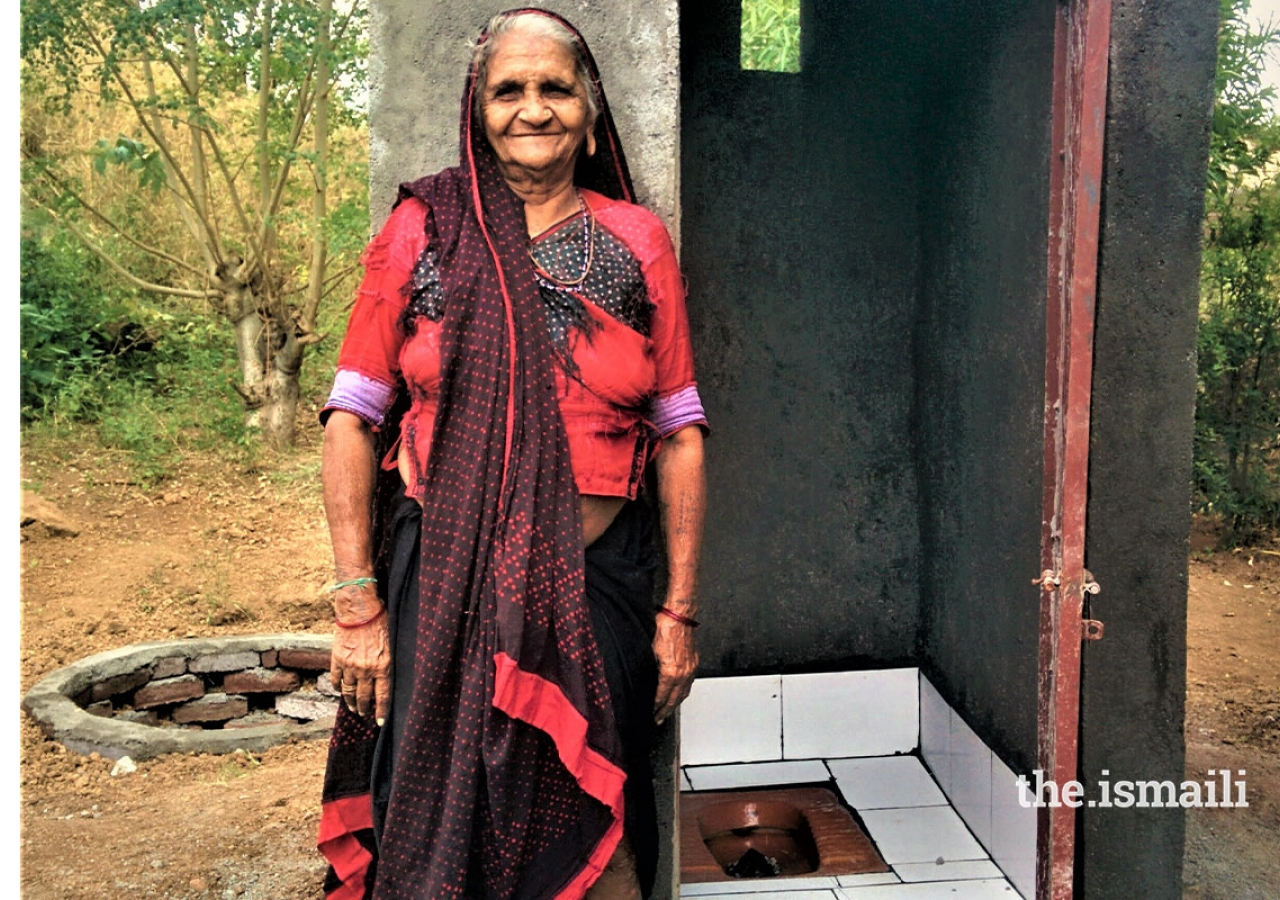 Mongi Maa from Zanjharda, Rajula with her under-construction toilet. The introduction of toilets has made a substantial difference to community health outcomes in areas where AKAHI has implemented its EHIP