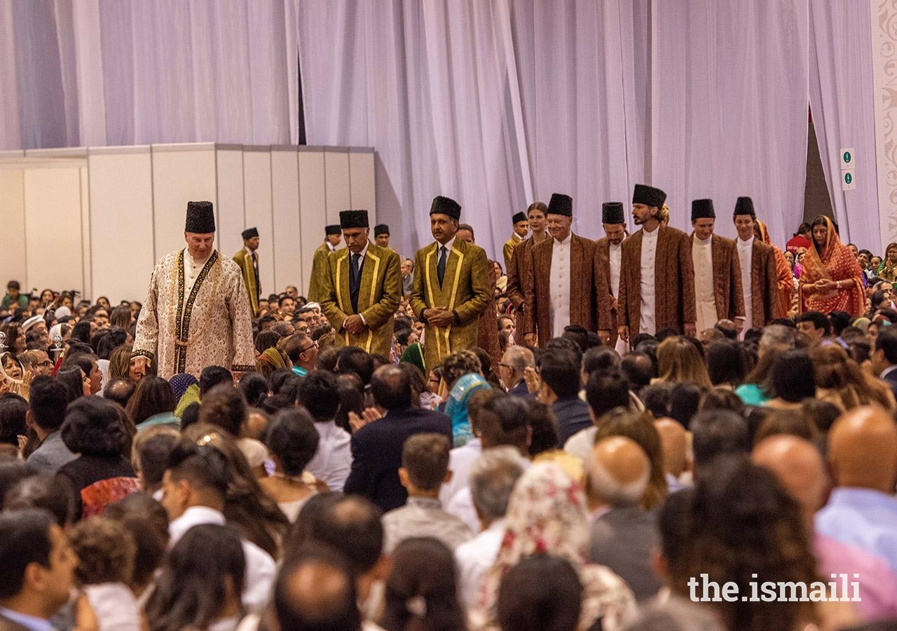 Mawlana Hazar Imam walks through the Jamat at the Diamond Jubilee Darbar in Lisbon, followed by Prince Amyn, Princess Zahra, Prince Rahim and Princess Salwa, Prince Hussain, Prince Aly Muhammad, Miss Sara Boyden, and Master Iliyan Boyden.