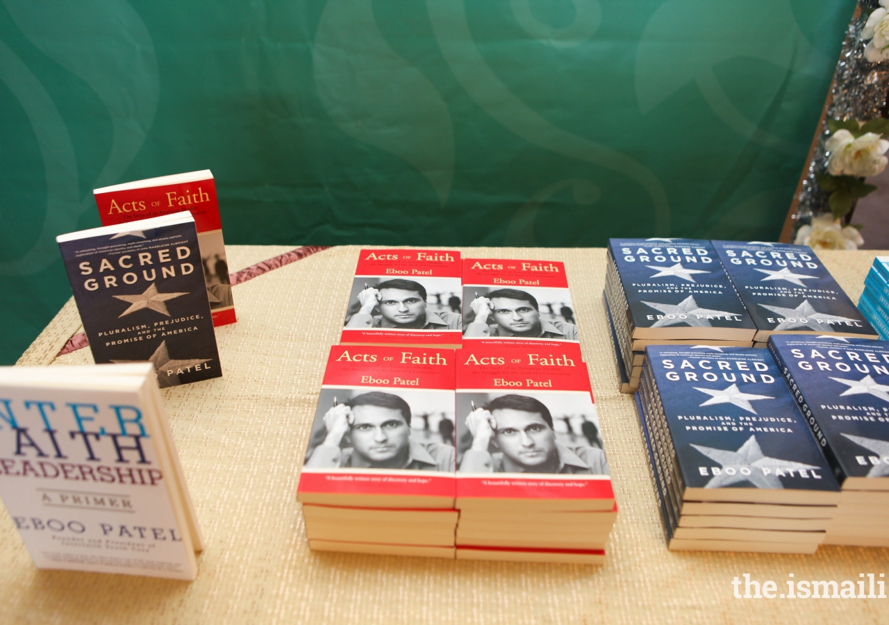 Books written by Dr. Eboo Patel are on display for the audience members to view.
