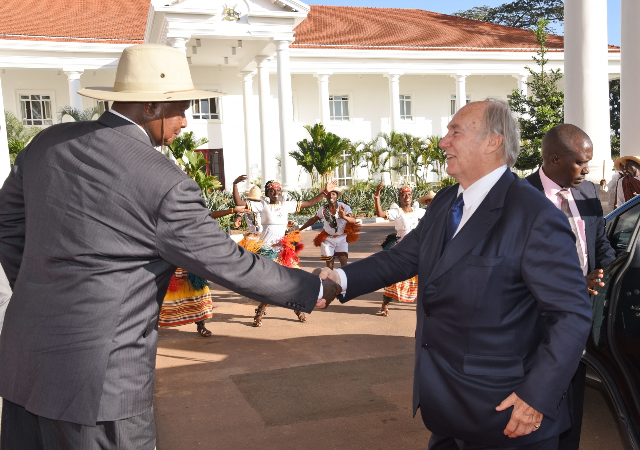 His Excellency President Yoweri Kaguta Museveni welcomes Mawlana Hazar Imam to the State House in Entebbe as traditional Ngoma dancers perform in the background.