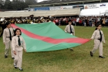 Young Ismaili girls and boys carry the Ismaili Flag with pride.