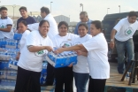 Volunteers from FOCUS Humanitarian Assistance unload water for people affected by Hurricane Ike at a Houston Point of Distribution.