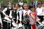 Just outside Khorog Park, a group of Tajik girls show off the new ice skates that will be available for use when the park pond freezes over in the winter.
