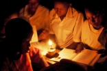 In the absence of electricity, students in a primary school classroom have to study using kerosene lamps.