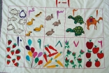 Numbers 1 – 10 in Dari with pictures sewn by mothers for the Sparks Early Childhood Development Program.