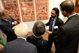 A guide explains the exhibition to guests at the Enlightened Encounters outreach event held at Chicago Headquarters Jamatkhana in Glenview, IL.