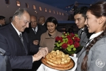 Mawlana Hazar Imam is presented with a traditional offering of non (bread) by two students from the Aga Khan School in Osh. Gary Otte