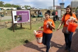 I-CERV volunteers carry orange buckets collecting funds in support of the Richmond Folk Festival.