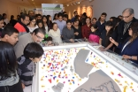 Visitors gather around the architectural-scale model of a historic district of Cairo that served as a centrepiece of the exhibition and was populated by houses designed and printed by 3D workshop participants. Vazir Karsan