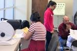 Jamati members get vision screenings.