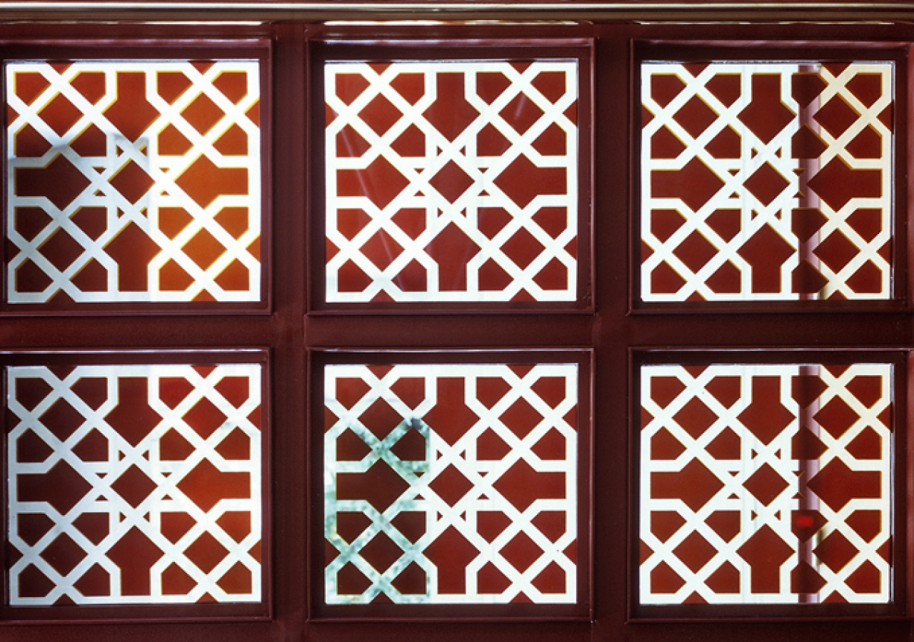 A detailed view of the window pane reveals intricate Islamic geometric patterns.