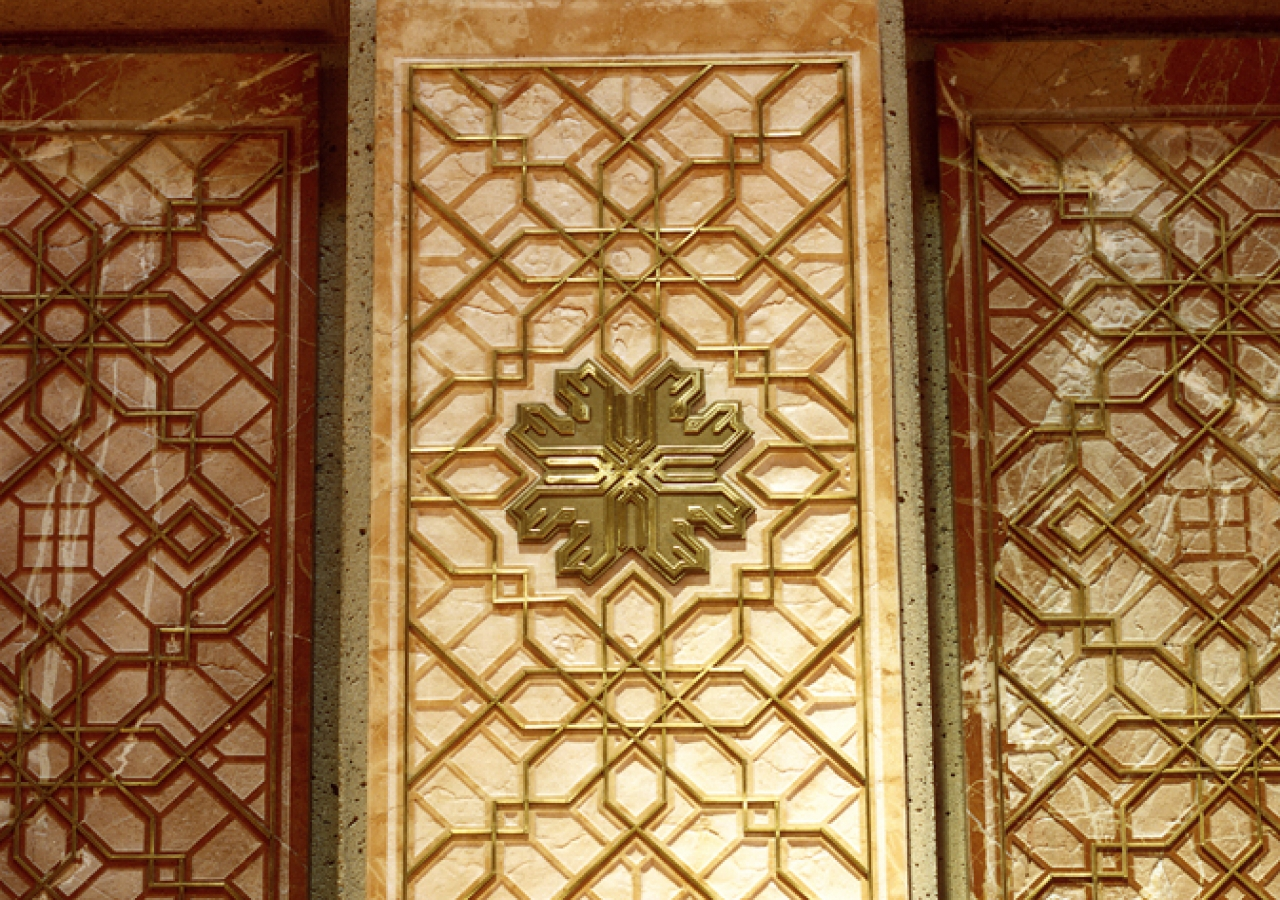 Sandblasted coral and rose marble panels inlaid with brass are used to form the mihrab, the Muslim architectural indication of the direction of prayer.