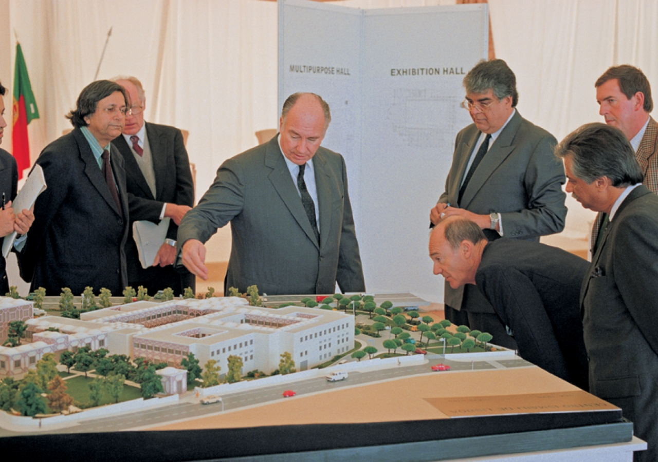 Mawlana Hazar Imam and Prince Amyn discuss the model of the Ismaili Centre, Lisbon as the architects and others look on.