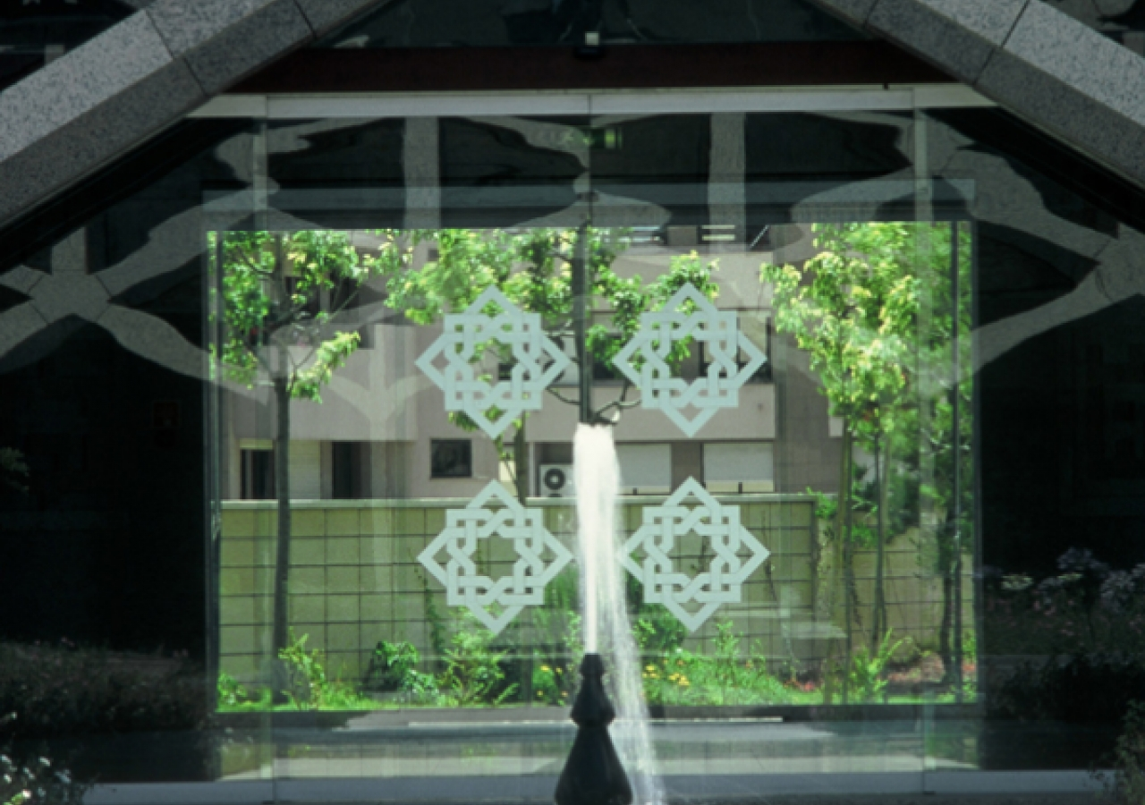 A courtyard fountain framed in granite lattice.