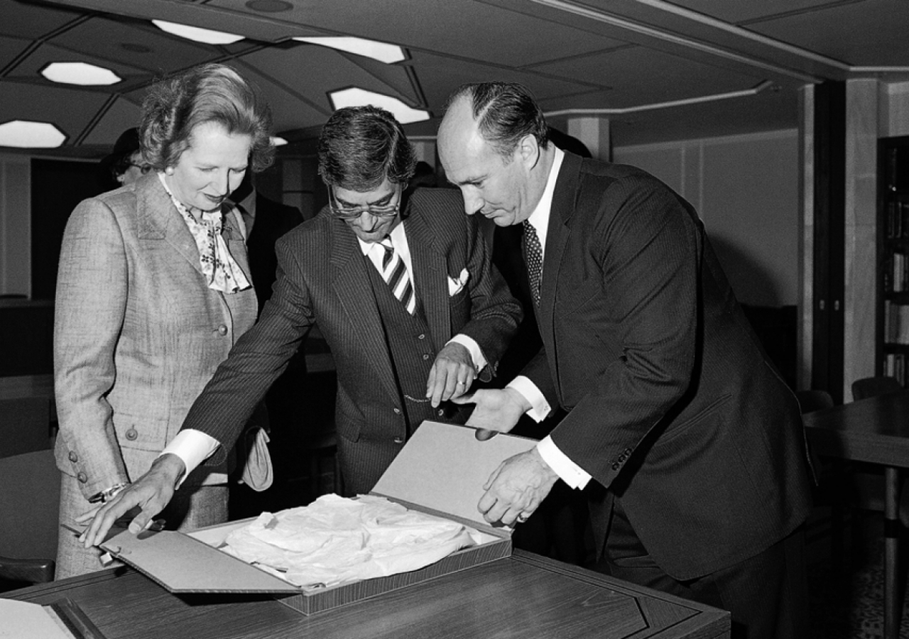 Mawlana Hazar Imam, Prime Minister Thatcher and Anil Ishani, President of the Ismaili Council for the United Kingdom, unpack a gift at the occasion of the opening of the Ismaili Centre, London.