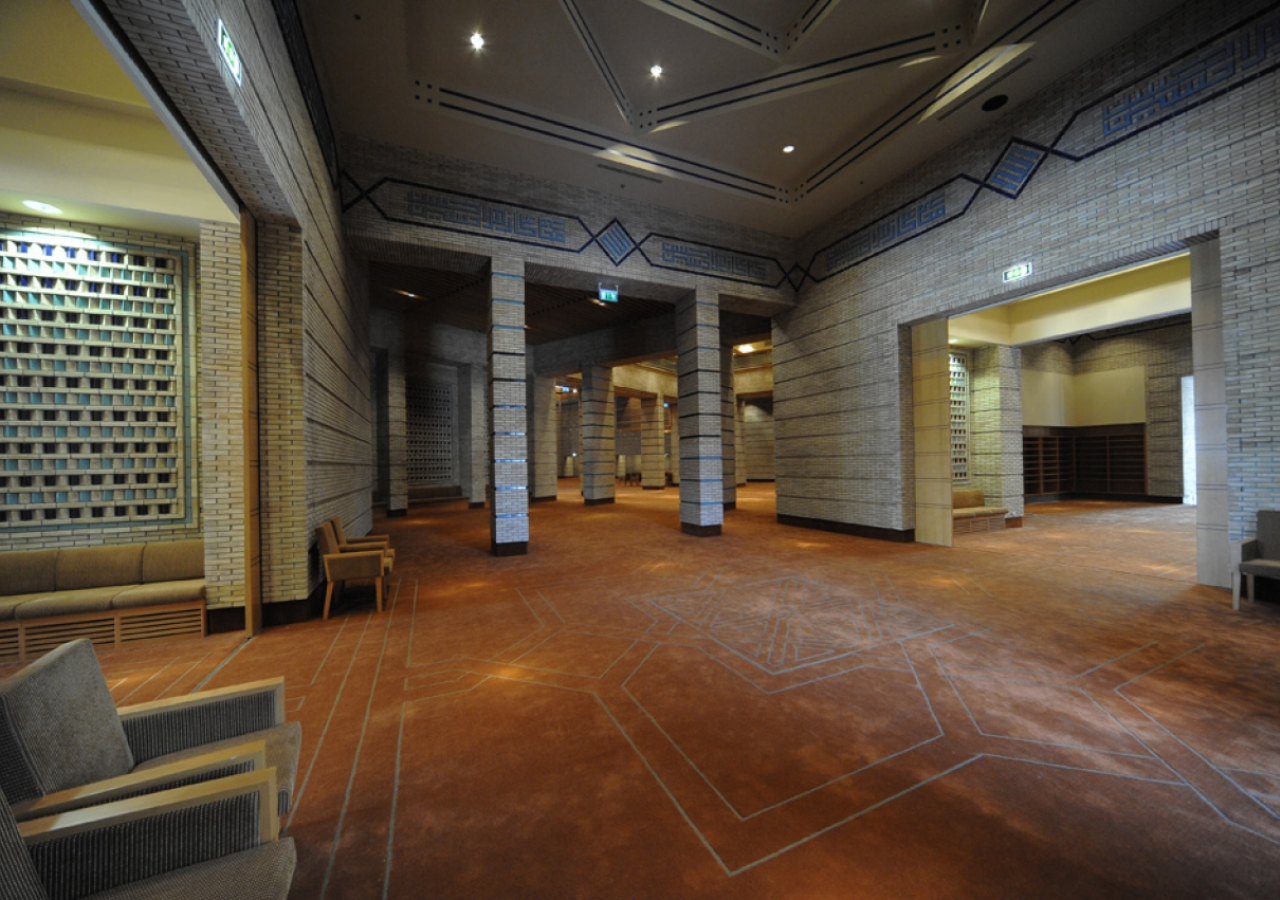 A view from the foyer towards the Prayer Hall Anteroom. Brick patterns and the calligraphy crowning the walls are among the prominent textures that characterise this space.
