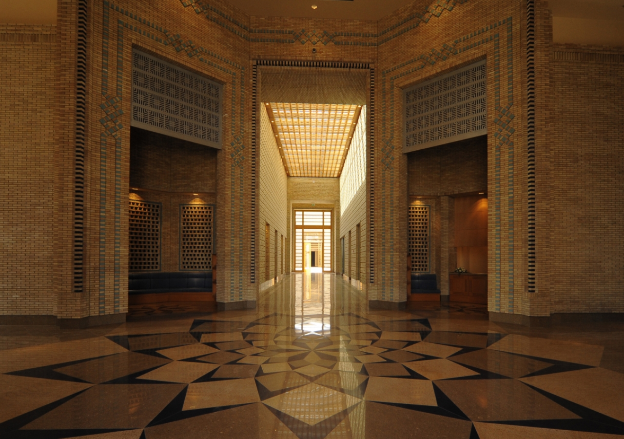 A view from the Main Entrance shows a seating alcove on the left, a reception desk on the right, and the axial corridor of the Administration area leading to the Great Courtyard.