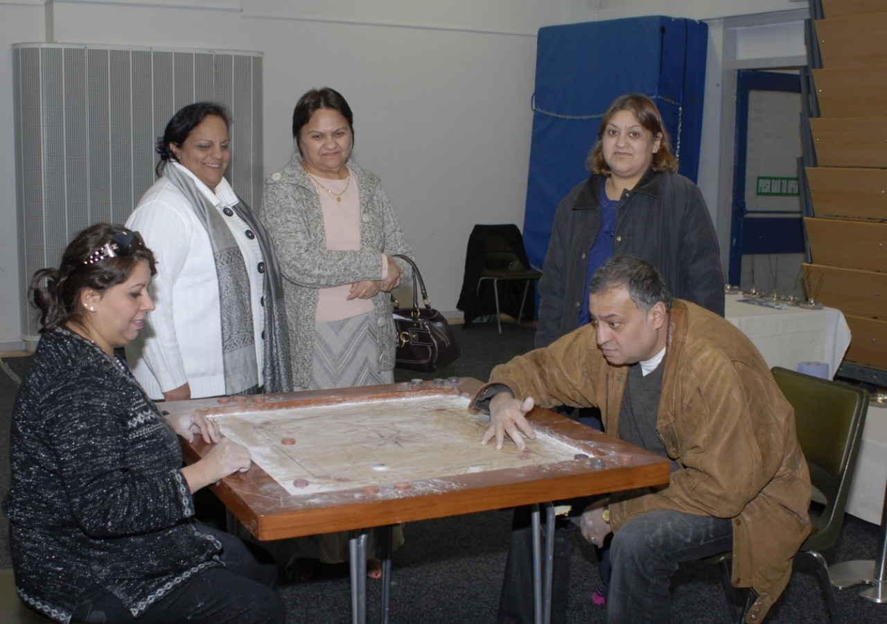 Seniors enjoying a traditional game of Carrom.